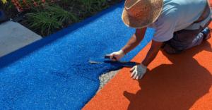 Landscaper installing sport court