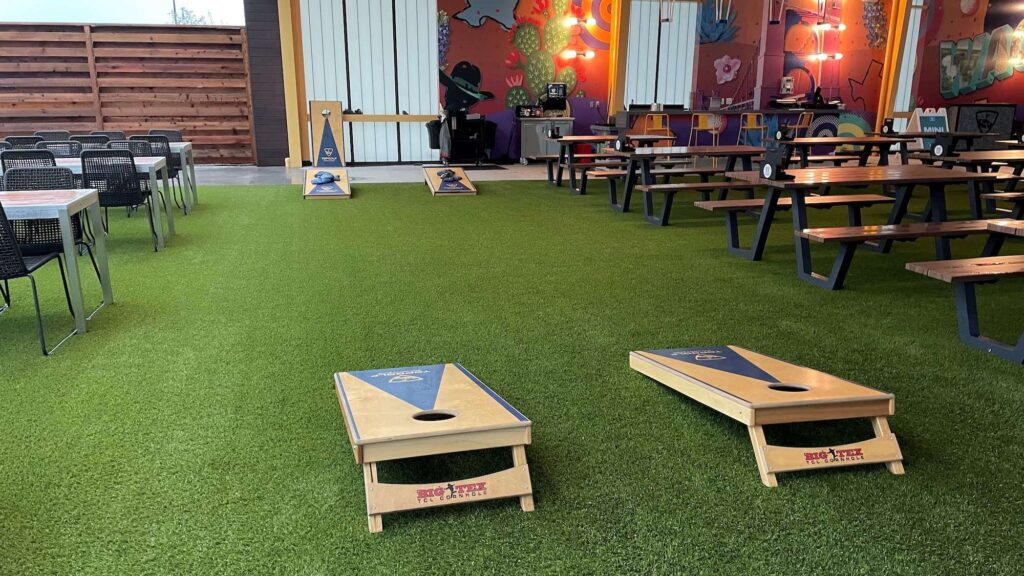 dining area with artificial turf and cornhole